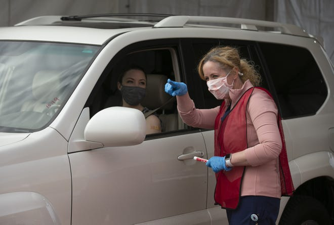 Dr. Cara Christ, director of the Arizona Department of Health Services, shows Emily Alexander, a fourth grade teacher, where to drive after she received a COVID-19 vaccine in the parking lot at Phoenix Municipal Stadium in Phoenix on Feb. 1, 2021.