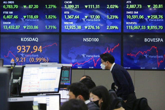 A currency trader watches monitors at the foreign exchange dealing room of the KEB Hana Bank headquarters in Seoul, South Korea, Monday, Feb. 1, 2021. Asian stock markets gained Monday after coronavirus vaccine maker AstraZeneca agreed to increase supplies to Europe amid rising worries about the disease.(AP Photo/Ahn Young-joon)