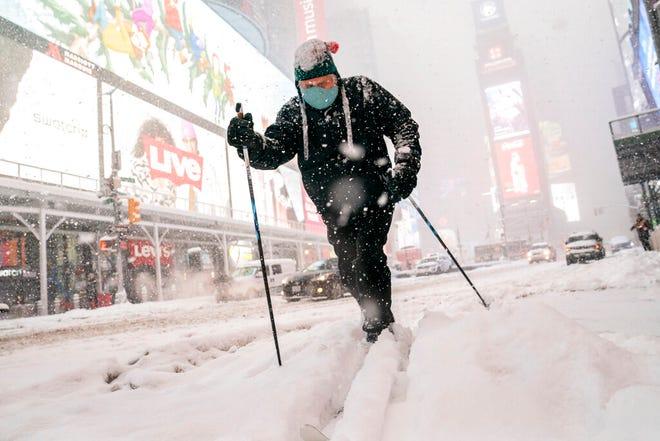 Steve Kent skis through Times Square during a snowstorm, Monday, Feb. 1, 2021, in the Manhattan borough of New York. (AP Photo/John Minchillo)