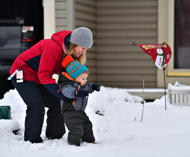 Lauren McAuliffe sets her 22-months-old son Miles down to walk in the snow during winter storm weather in Windsor Township, Monday, Feb. 1, 2021. Dawn J. Sagert photo