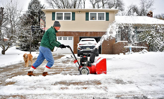 David Weaver uses a snow blower to clear his driveway while his golden retriever Penny, 10, looks on during winter storm weather in York Township, Monday, Feb. 1, 2021. Dawn J. Sagert photo