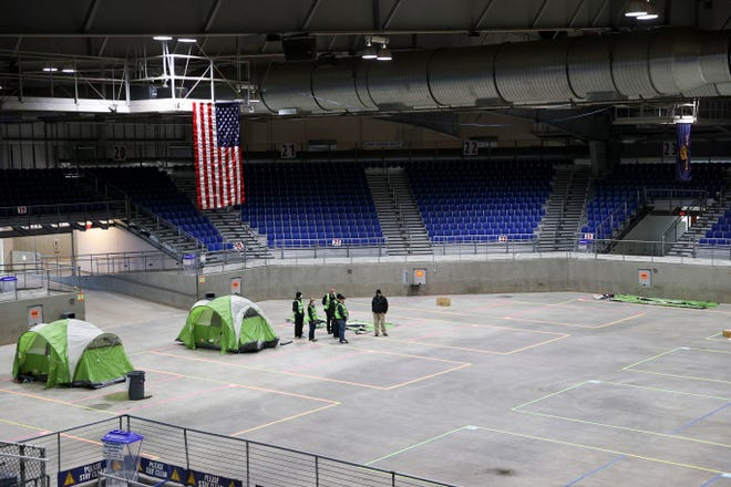 Workers begin to set up tents inside the Pavilion at the Oregon State Fairgrounds on Monday. The building will house a temporary homeless shelter for 100 people and be operated by Church at the Park.