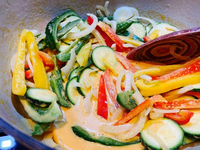 Colorful bell peppers, zucchini and onions cooking coconut milk in Thai red curry dish.