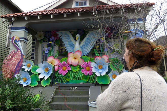 Designer Caroline Thomas looks at a house decorated like a parade float in New Orleans. All around the city, thousands of houses were decorated as floats because the coronavirus pandemic has canceled parades that usually take place on Mardi Gras.