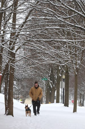 Robert Behrens walks his dog Roxie along Girard Street Monday in Akron.