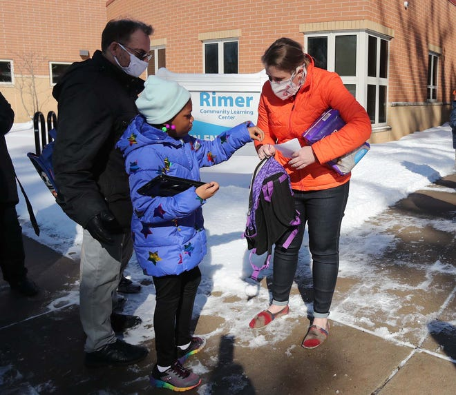 Terry Lilley, left, an educational assistant and Kelly Haslam, an intermediate Achieve teacher greet student Journee Blackmon as she arrives for her class Tuesday at Rimer Community Learning Center as part of the Akron Public Schools Remote Plus program.