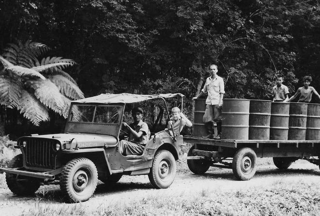 Joe Huber Jr., 12, rides in the back of a jeep towing drums of latex from the field to the processing mill at Goodyear's Pathfinder plantation in the southern Philippines in early 1947.