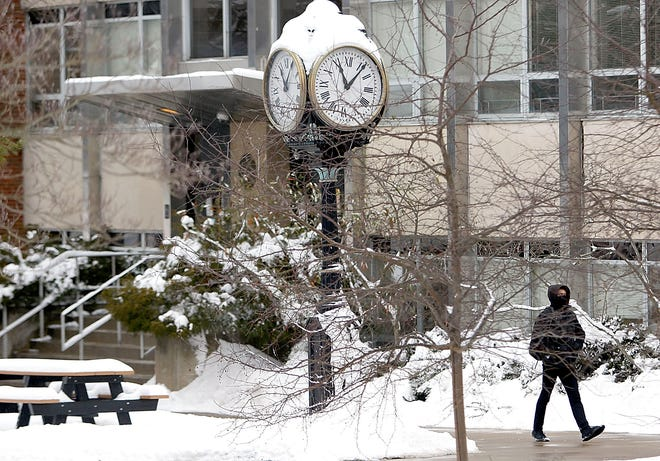 An Ashland University student walks past the now covered clock on the quad on Tuesday, Feb. 2, 2021. TOM E. PUSKAR/TIMES-GAZETTE.COM