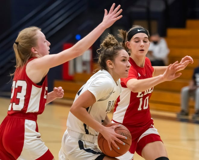 Rochester's Corynne Hauser gets through Eden Christian Academy's Katie Kirby, left, and Natalie Merrick during their game Monday at Rochester High School.