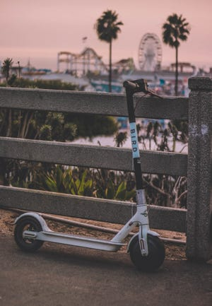 A Bird electric scooter is shown leaning on a fence in Bartlesville, Oklahoma. The four-year-old scooter company is hoping to enter into a partnership with the City of Monroe.