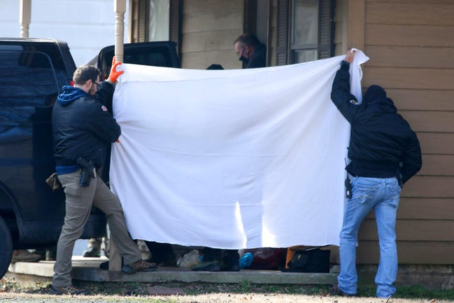 Investigators block the public's view as bodies are removed from the scene of a shooting on Tuesday, Feb. 2, 2021 in Muskogee, Okla.  Police say one person is in custody after  six people, including five young children, were shot to death at a home about 45 miles southeast of Tulsa. (Mike Simons/Tulsa World via AP)