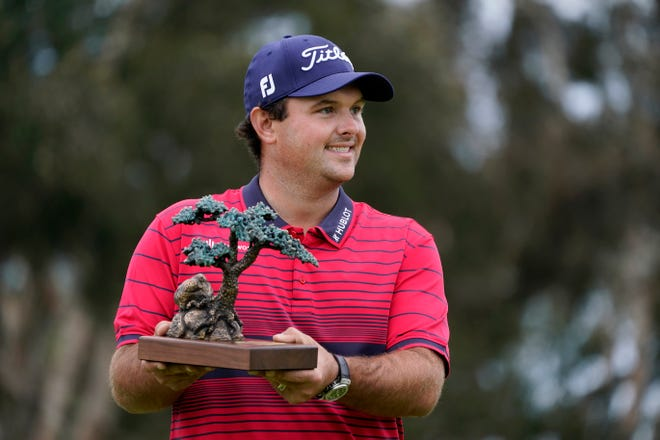 Patrick Reed holds his trophy for winning the Farmers Insurance Open at Torrey Pines on Sunday.