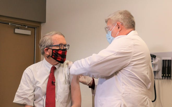 Gov. Mike DeWine receives a COVID-19 vaccination from his family physician, Dr.  Kevin Sharrett, at his office in Jamestown in Greene County.