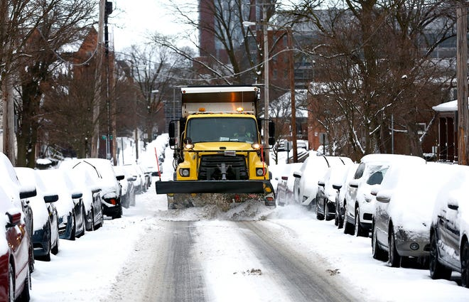 A snow plow cleans W. 10th Ave., a side street near Ohio State University in Columbus on Tuesday. The morning temperature was 23 degrees; temperatures are predicted to be in the 20's on Wednesday.