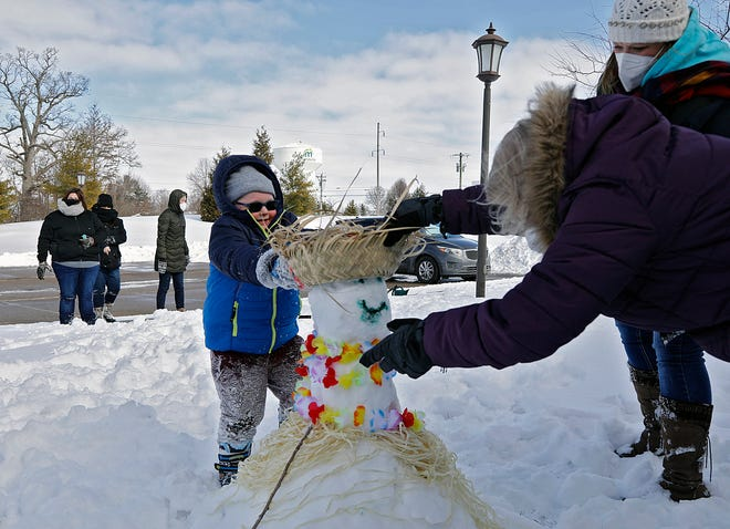Parker Phipps, 4, adds a hat to a snowman with help from Kathy Strohm, front right, and Lisa Brown, back right, as staffers and their families make snowmen outside the rooms at Brookdale, a senior living facility, in Marysville on Tuesday.