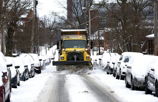 A snow plow cleans West 10th Avenue, a side street near Ohio State University, on Tuesday.