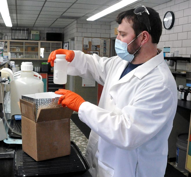 Cody Bower, a lab technician at the Wooster Wastewater Pollution Plant, places the bottle containing a sample of wastewater taken on Tuesday into an insulated box.