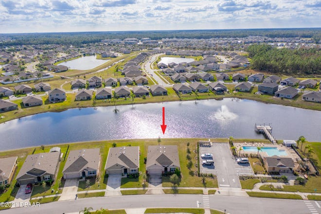 This four-bedroom, two-bath waterfront home in Port Orange offers lake views from the living area and lake fountain views from the rear patio.