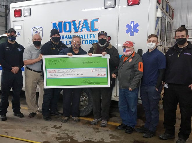 From left are Jason Kane, Kelly Brown and Robert Parry of the Mohawk Valley Ambulance Corps; Herkimer Elks Lodge 1439 Exalted Ruler Roy Henry, presenting MOVAC with a $2,500 donation; and Ray Lenarcic, Herkimer County Hunger Coalition founder, presenting MOVAC with a $1,000 check;  Hunger Coalition Director Ron Schoonmaker; and Dean Picente and Don Healey of MOVAC.
