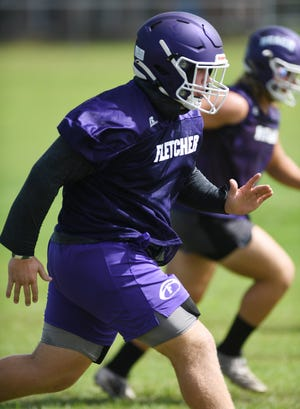 Fletcher offensive lineman Chandler Kirton warms up with teammates at the start of a high school football preseason practice session. Kirton, who is scheduled to sign with Austin Peay, is among dozens of Jacksonville-area athletes on course to confirm their futures in college athletes on National Signing Day Wednesday.
