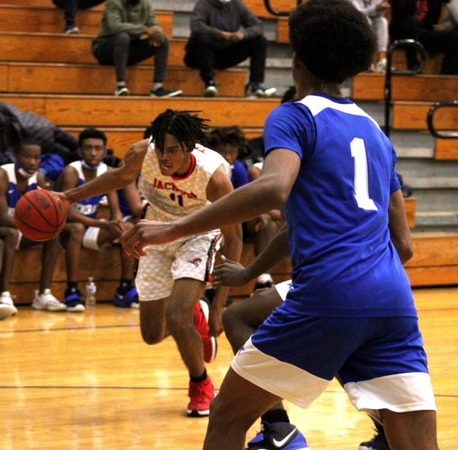 Jackson forward Bryce Turner (11) dribbles as Lee forward Jarrion Smith (1) defends during the Gateway Conference boys basketball semifinal. Jackson rallied from 12 points down to win.