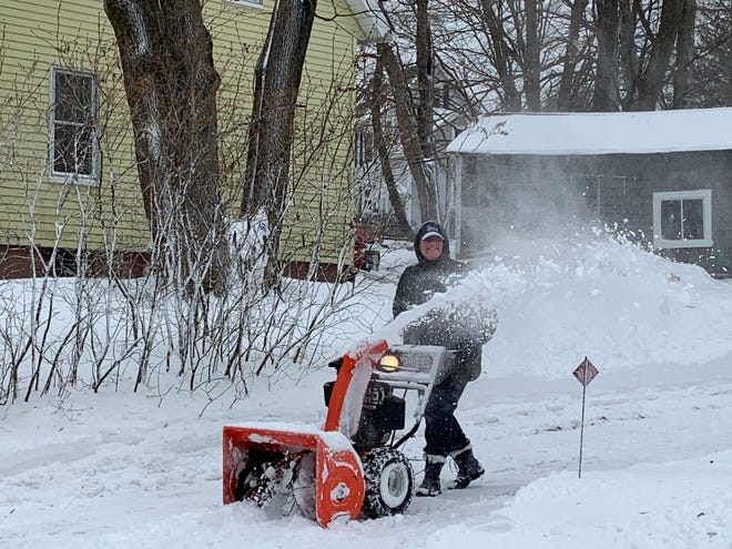A resident on Lennon Street in Gardner clears her driveway after this week's nor'easter.