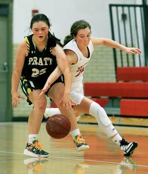 Pratt's Lexi Walker (23) and Trinity Catholic's Hayley Hughes (24) grab for the ball during their game Monday night. Trinity defeated Pratt 63-40.