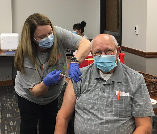 Meggan Donham RN, Assistant Director of Nursing at PrairieStar Health Center, administers the Moderna COVID-19 vaccine to Loyd Farr. The health provider has opened registration for its patients age 65 and older to receive the vaccine. It plans to administer at least 100 a week.