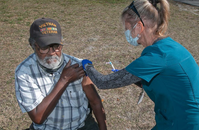 Lakeland resident and Vietnam War veteran William Mills, 70, receives his COVID-19 vaccination on Tuesday from Susan Gatto, a registered nurse with the Florida Health Department in Polk County, during the drive-up distribution site at First Baptist Institutional Church on Martin Luther King Jr. Avenue in Lakeland on Tuesday. Mills was a walk-up patient.