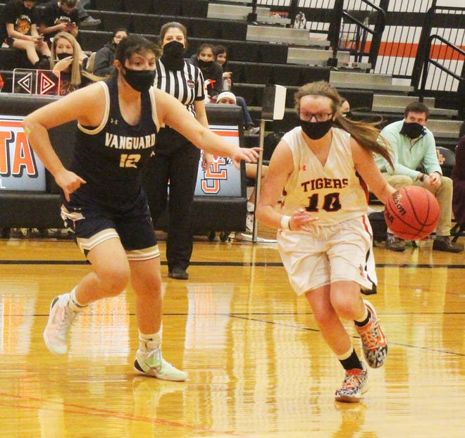 La Junta High School's Sierra Reisch moves past Vanguard's Whitney Richardi (12) in Monday's game at Tiger Gym. Reisch scored 13 points, but the Tigers lost 89-28.