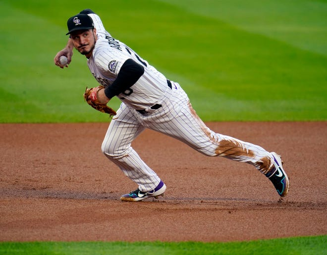 FILE - In this Sept. 11, 2020, file photo, Colorado Rockies third baseman Nolan Arenado throws to first during the first inning of a baseball game against the Los Angeles Angels in Denver.