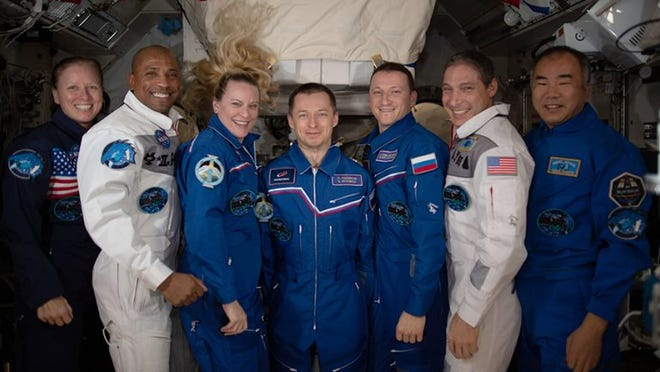 The seven-member Expedition 64 crew poses for a portrait inside the space station's Kibo laboratory module.