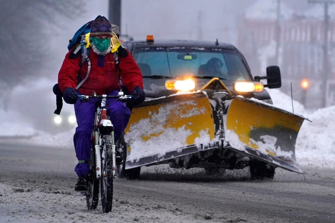 A bicyclist peddles on slick roads during a winter snow storm, Tuesday, Feb. 2, 2021, in Brunswick, Maine. (AP Photo/Robert F. Bukaty)