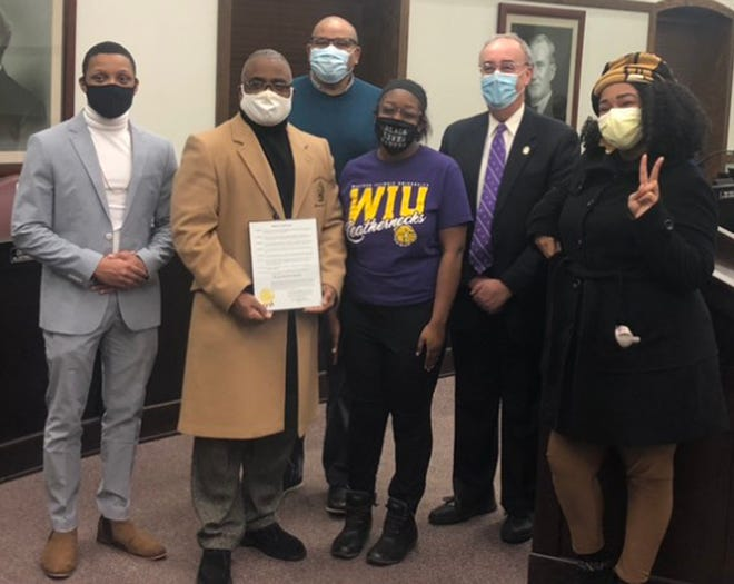 (Left to right): Antonio Carter, Byron Oden-Shabazz, Carl Ervin, Shakyria Bailey, Mike Inman, and Kwyn Townsend Riley pose with the proclamation during Monday's city council meeting.