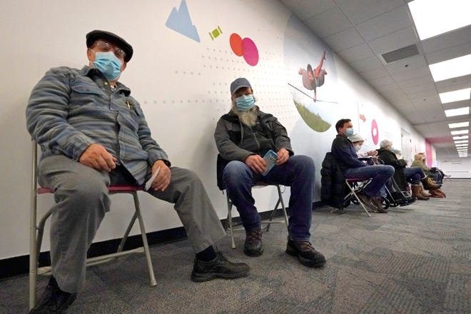 Gino Ferrusi, 78, far left, sits in a recovery area with others after receiving a COVID-19 vaccine at a regional vaccination site, Feb. 1, 2021, in Wakefield.