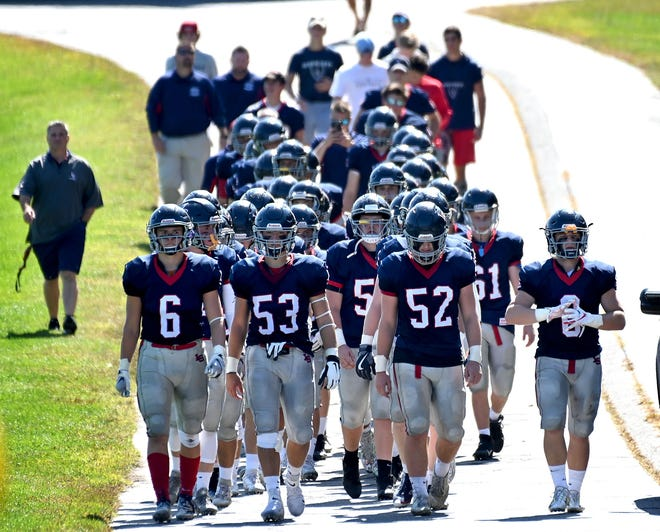 The Lincoln-Sudbury football team walks from the locker room to   its home field for a game against Melrose in 2019. High school football teams won't be allowed to use locker rooms during the Fall II season that starts in late February.