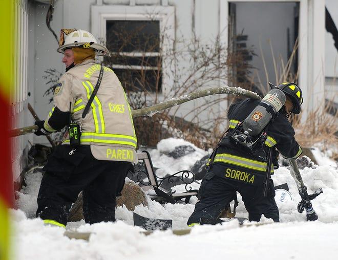 Northborough Fire Chief David Parenti (left) and Marlboroigh firefighter Dana Soroka pull hoses during barn fire at the Hillside School Farm in Marlborough, Feb. 2, 2021.