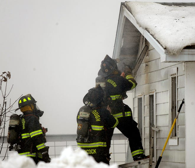 Marlborough firefighters use a chainsaw to vent the building during a barn fire at the Hillside School Farm in Marlborough, Feb. 2, 2021.