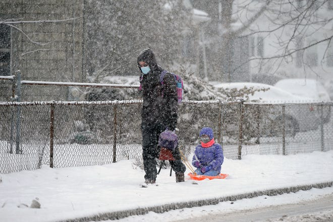 Zahar Raskin, and his daughter in tow, Olivia, 6, of Natick, make their way along East Central Street, Feb. 1, 2021.