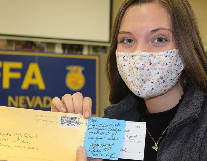 Nevada High School agriculture education student and FFA member Chloe Peterson holds the envelope and check for $1,000 donation from Tom and Teri Burke.