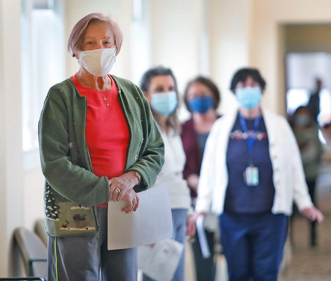Regina Lisinski waits in line for her first of two vaccine doses at Fairing Way assisted living facility in South Weymouth.