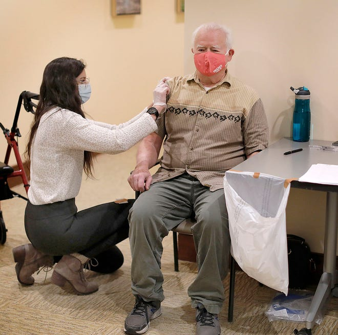 Earl Anspach, 75 gets ready for a vaccine from Melissa Canitez of Walgreens.