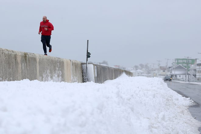 A jogger runs along the barrier of Hampton Beach after a snow storm earlier in 2021 left many residents with several inches of snow.