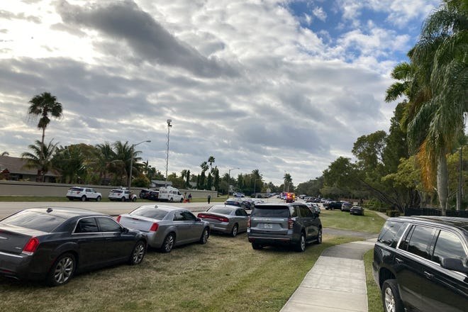 Vehicles are parked near a roadblock Tuesday, Feb. 2, 2021, in Sunrise, Fla. Police in South Florida have swarmed a neighborhood following a Tuesday morning shooting involving FBI agents