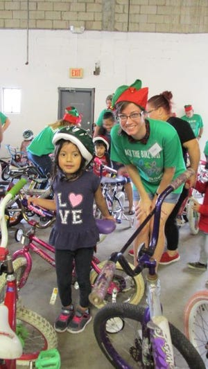 Jack the Bike Man and volunteers fit hundreds of children from economically challenged families for free bicycles and helmets at a festive event in late December.