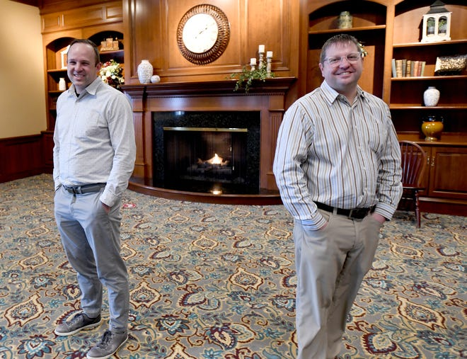Zach Coblentz (left) stands with his cousin Gary Sommers in the lobby of Hartville Kitchen, one of the destination businesses that are part of HRM Enterprises. Sommers is chief executive officer at HRM, while Coblentz is chief operating officer.