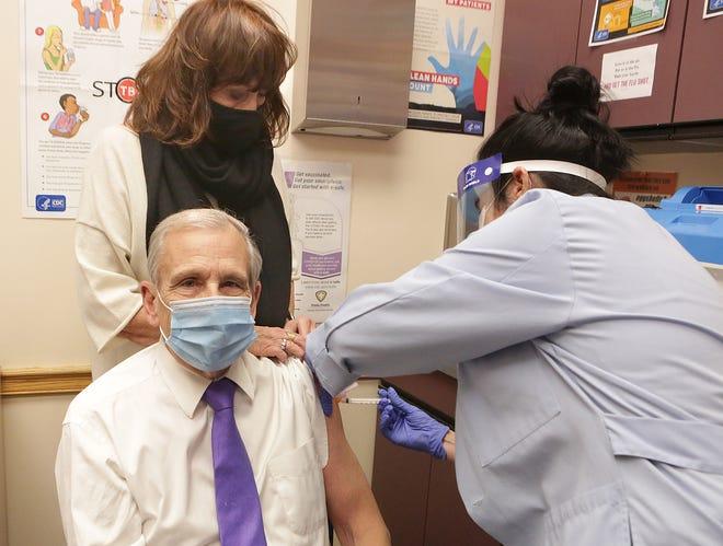 Canton Mayor Thomas Bernabei receives the first shot of the Moderna COVID-19 vaccine from Canton City Public Health Nurse Tammy Stolicny as the mayor's wife, Bebe Bernabei, looks on.