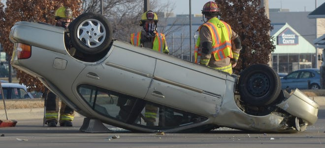Emergency responders evaluate the damage to a tan vehicle that rolled over on S. 9th Street in front of Walmart about 4:22 p.m. in Salina on Monday. Salina police diverted southbound traffic temporarily. The driver was able to escape the vehicle with no injuries.