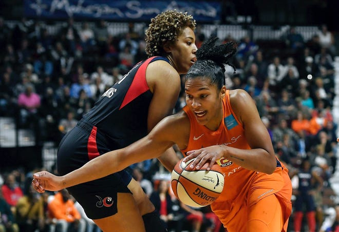 Connecticut Sun's Alyssa Thomas, front, drives past Washington Mystics' Tianna Hawkins during the first half in Game 4 of basketball's WNBA Finals, Tuesday, Oct. 8, 2019, in Uncasville, Conn.