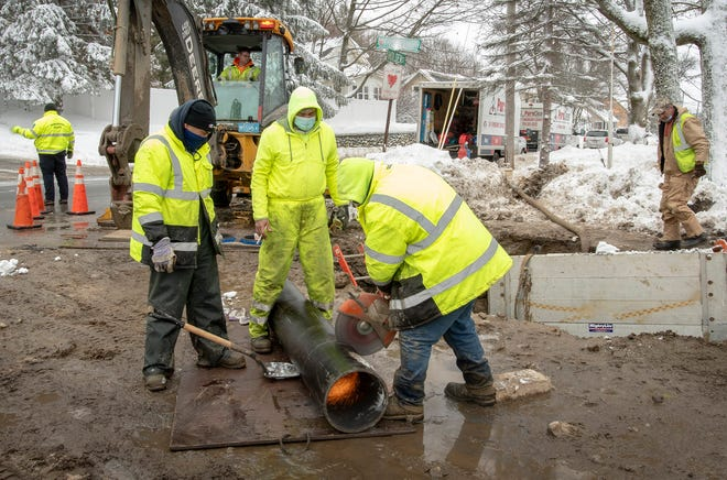 Department of Public Works & Parks water division workers cut a section of 12-inch pipe to repair a broken water main at the corner of Holden Street and Frederickson Avenue Tuesday.